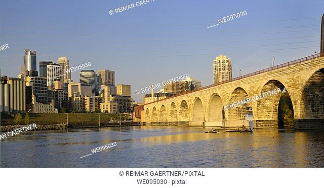 Minneapolis highrise tower skyline and the Stone Arch Bridge on the Mississippi at sunrise