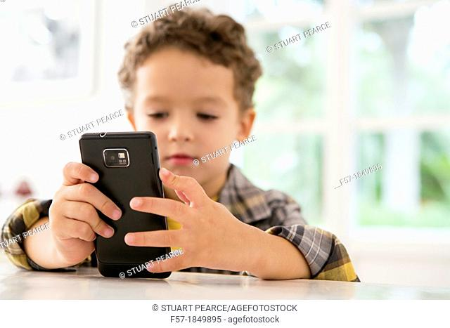 Four year old boy playing games on a cell phone