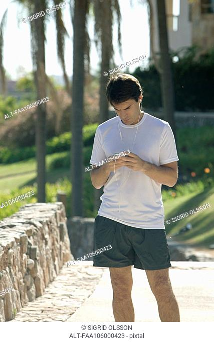 Jogger checking smartphone in park