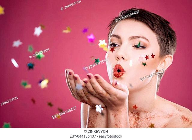 So happy. Delighted charmign woman blowing tinsels while posing against pink background