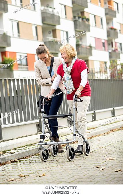 Adult granddaughter assisting her grandmother walking with wheeled walker