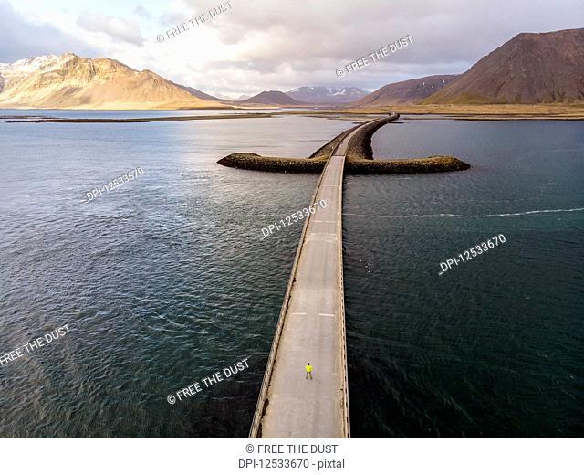 Man standing on bridge in Iceland. Image taken with a drone; Grundarfjorour, Iceland