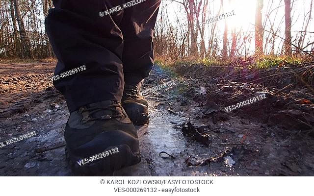 Walking and braking the ice on the forest dirt road near Lublin, Lubelskie, Poland