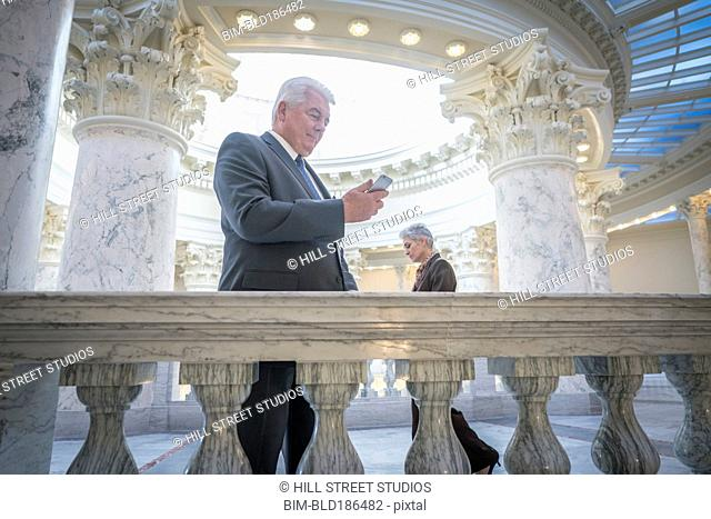 Caucasian senator using cell phone in capitol