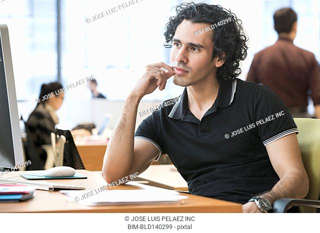 Businessman thinking at desk in office