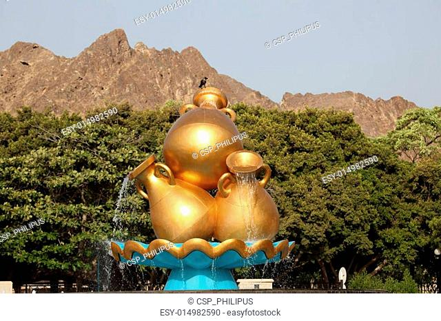 Golden water jugs at a roundabout in Muscat, Oman