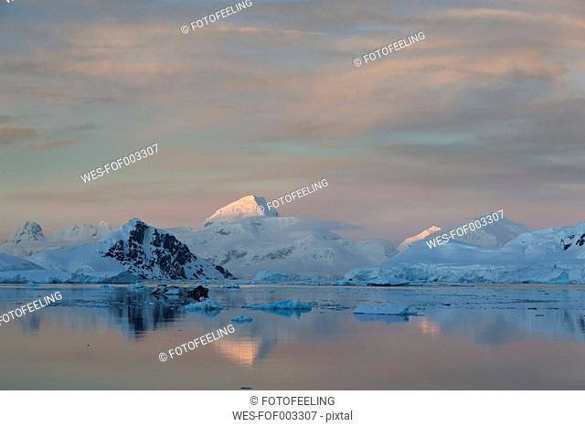 South Atlantic Ocean, Antarctica, Antarctic Peninsula, Lemaire Channel, View of snow coverd mountain range at dawn