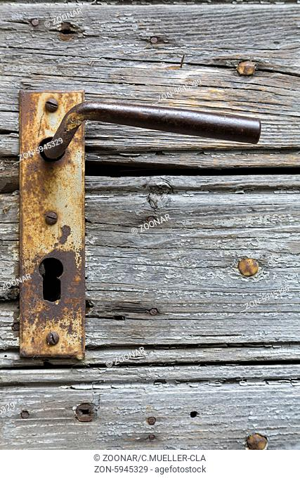 A wooden door with an rusty handle in it