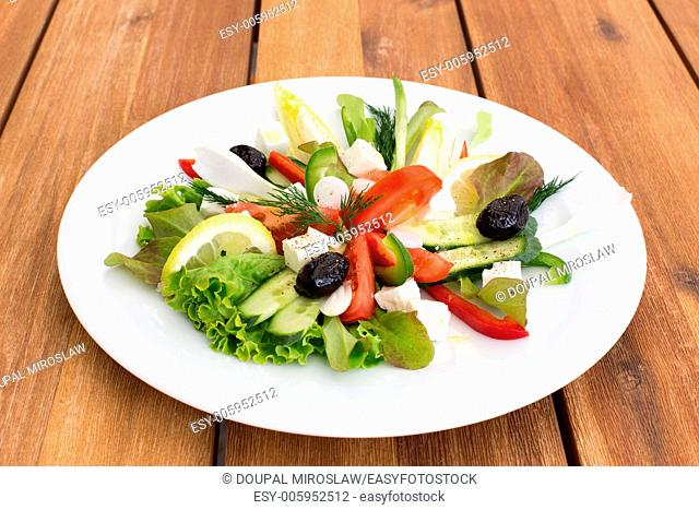 Greek salad with feta, tomatoes, cucumber, peppers and black olives on a wooden table