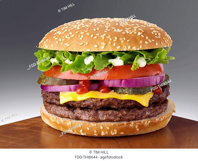 Cheeseburger with two beef patties lettuce red onion gherkin mayonnaise and tomato ketchup