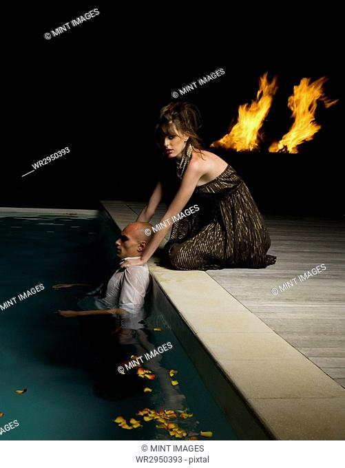 Woman kneeling on the edge of a swimming pool, touching shoulders of man inside pool, flames in the background