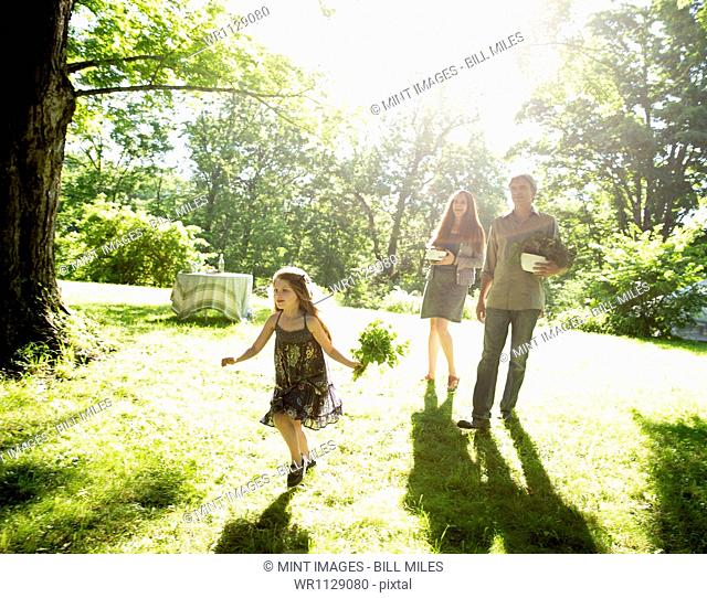 Outdoors in summer. On the farm. Two adults carrying cartons of fresh vegetables and plants. A girl carrying bunches of fresh herbs
