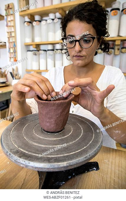 Woman sculpting a cup with clay in a ceramic workshop