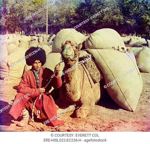 Central Asian camel driver poses with a camel loaded with packs ca. 1910. LC-DIG-prokc-20011