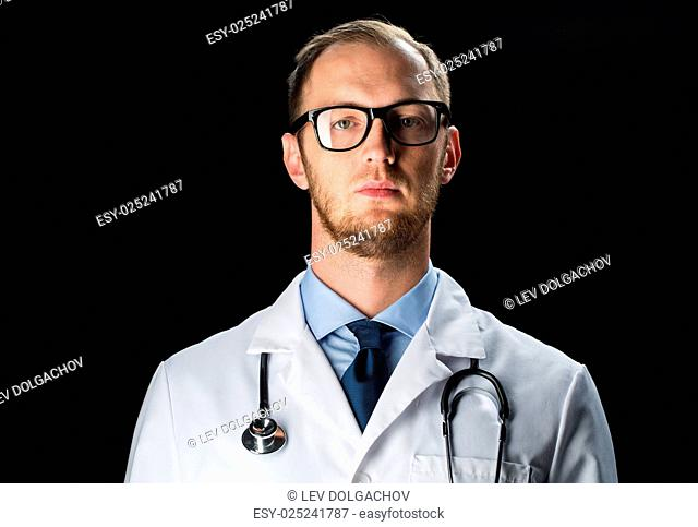 healthcare, people, profession and medicine concept - close up of male doctor in white coat with stethoscope over black background