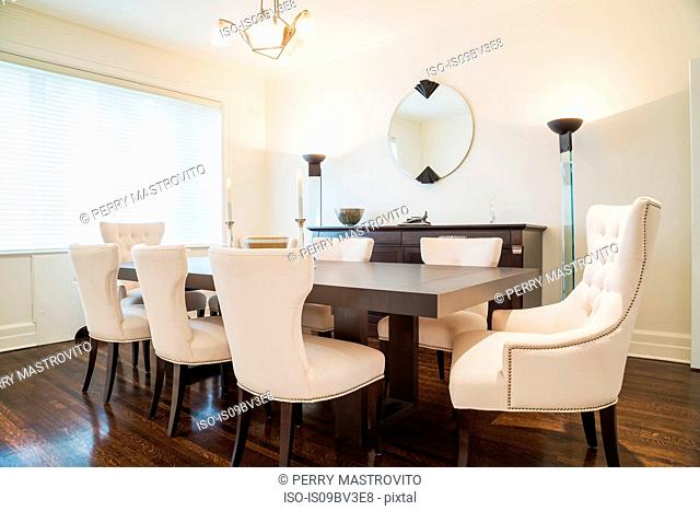 Dark wood dining table with white cloth upholstered chairs in dining room, dark stained wood flooring