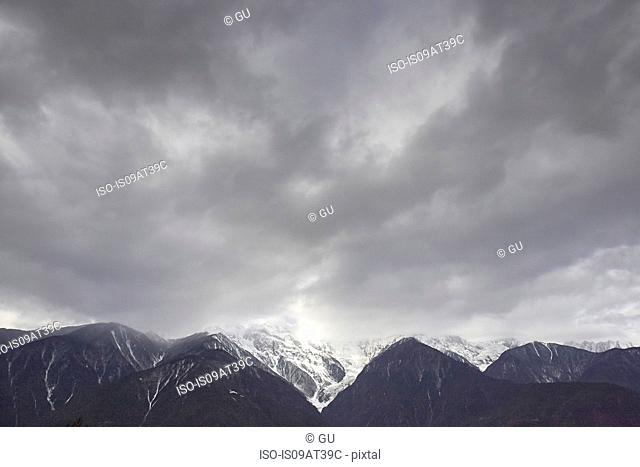 Dramatic cloudy sky and snow capped mountain range, Shangri-la County, Yunnan, China