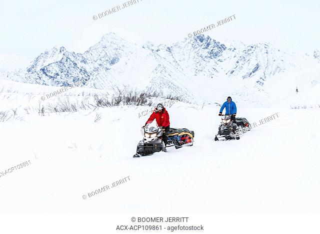 Two snowmobiliers making their way along the Canol Heritage Trail travel through the McKenzie Mountains near the Yukon and North West Territory border