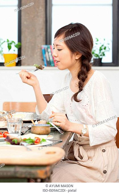 Young woman having lunch at table