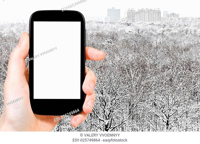 travel concept - hand holds smartphone with cut out screen and snowy forest and city on background