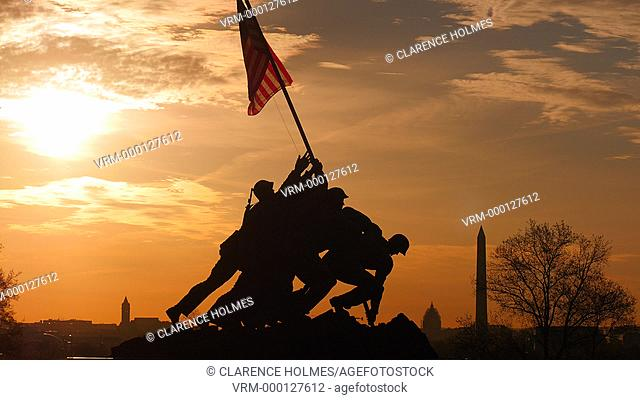 ARLINGTON, VA - APRIL 15: The Marine Corps War Memorial is silhouetted against an orange colored sky, with the Washington Monument and US Capitol visible in the...