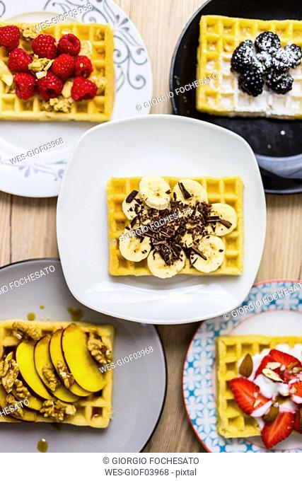 Plates of waffles with various toppings