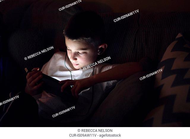 Boy on sofa wearing earphones looking down using digital tablet