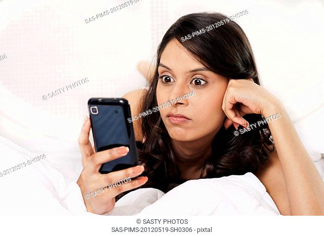 Woman text messaging on a mobile phone and looking angry