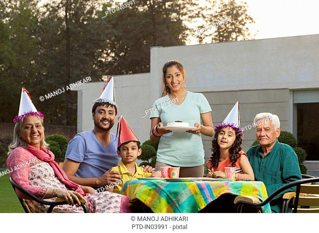 India, Children (4-5, 6-7) with parents and grandparents sitting at birthday table on backyard