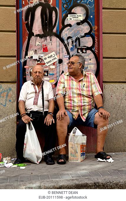 Two visitors to the El Rastro Flea market take a rest from shopping
