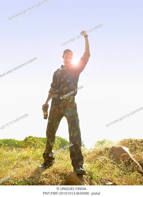 Soldier standing in a field celebrating his success