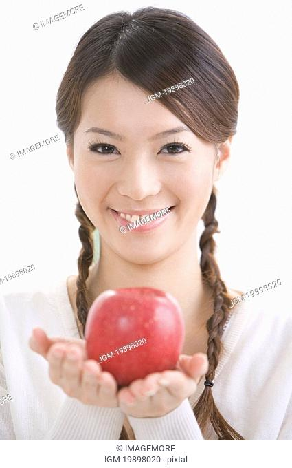 Young woman holding a red apple, portrait