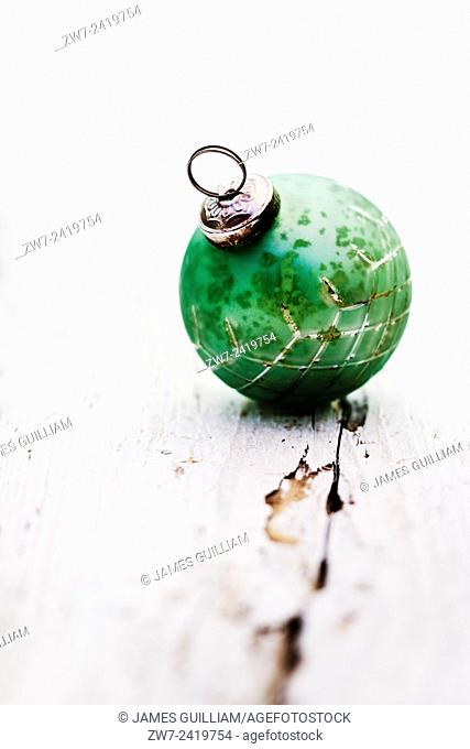 Antique glass Christmas tree trim resting on weathered wooden surface