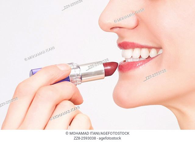 Close up of a young woman applying make up lipstick