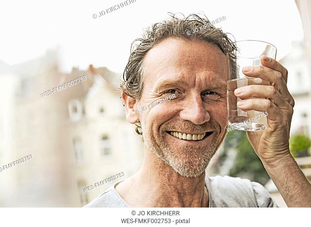 Portrait of smiling man toasting with water glass