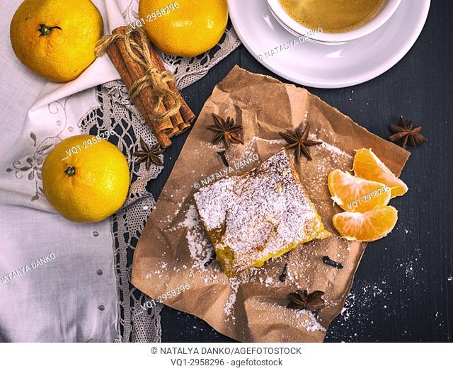 tangerine pie sprinkled with powdered sugar, fresh tangerines, next to a round cup with coffee, top view