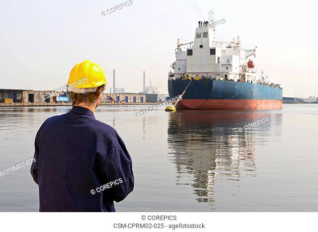 Docker looking at a moored off oil tanker, with his back to the camera