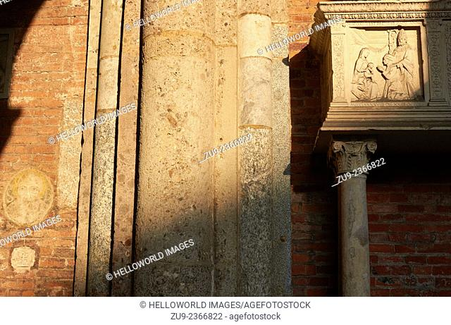 Carvings and artwork around entrance to red brick Romanesque Basilica of Sant Ambrogio, Milan, Lombardy, Italy, Europe