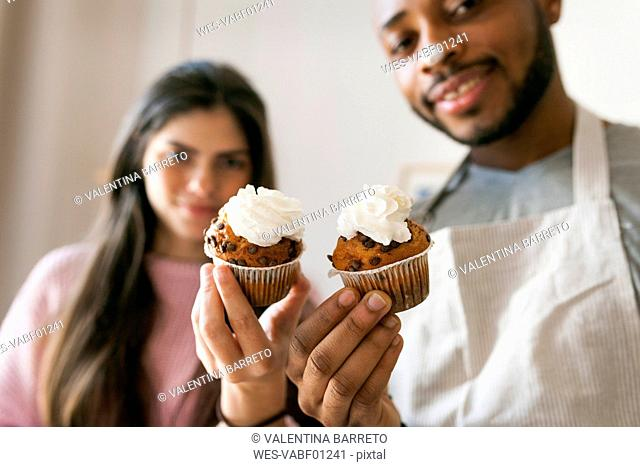 Young couple holding fresh cup cakes