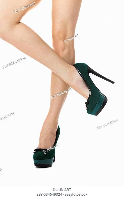Close up Sexy Flawless Woman Legs in Green High Heel Shoes with One Leg Lifted and Crossing the Other Leg. Isolated on White Background