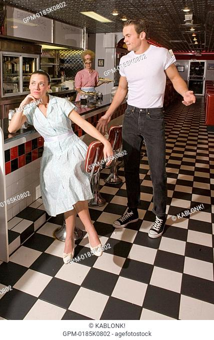 Young woman sitting at counter in old-fashioned diner ignoring young man behind her, 1950s style clothing