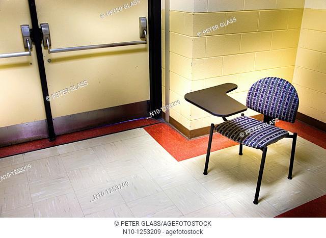 Empty deskchair in a college hallway