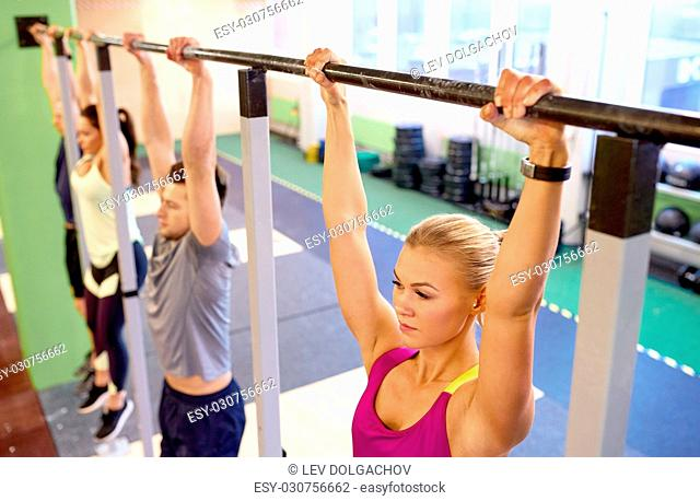 sport, fitness, exercising and people concept - woman with heart-rate tracker hanging on horizontal bar at group training in gym