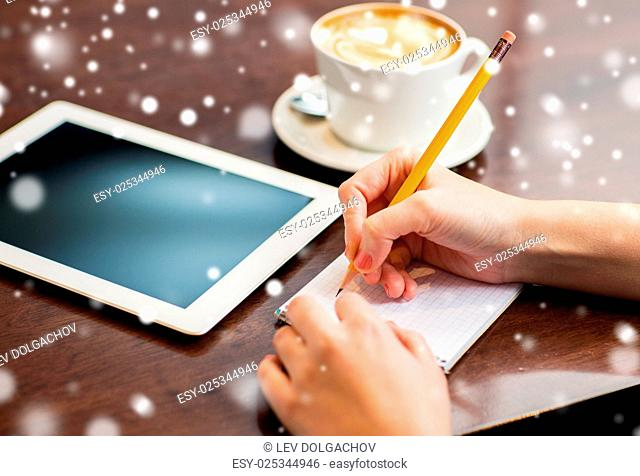 business, education, people and technology concept - woman hands writing to notebook by pencil and tablet pc computer with coffee over snow