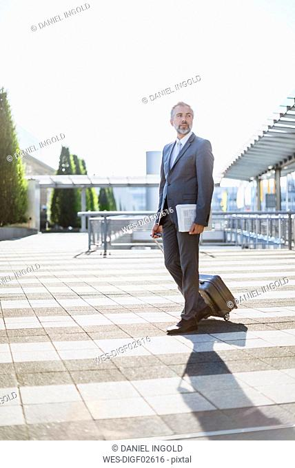 Businessman pulling rolling suitcase outdoors