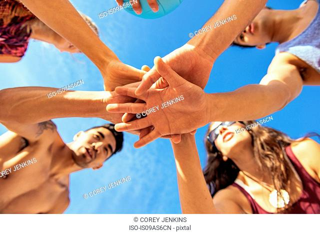 Group of friends joining hands on beach, low angle view