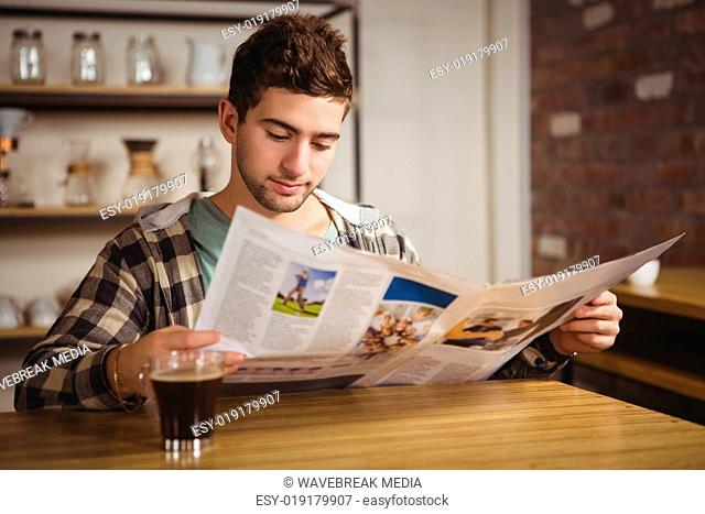 Hipster having coffee and reading newspaper