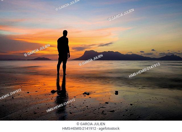 Malaysia, Borneo, Sarawak, Bako National Park, silhouette of a man in the sea contemplating the sunset at Telok Assam beach