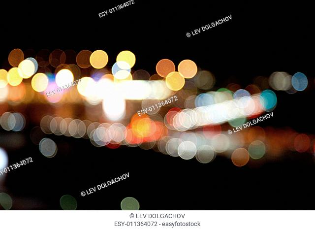 holidays, illumination and electricity concept - colorful bright lights on dark night background