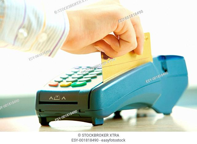 Close-up of human hand putting credit card into payment machine in shopping center